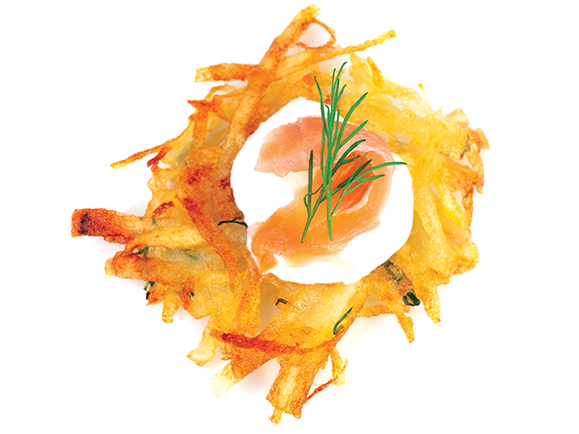 Bite sized potato rosti appetizer topped with fresh sour cream, smoked salmon and dill viewed from directly above